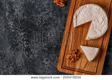 Camembert Cheese On Cutting Board.