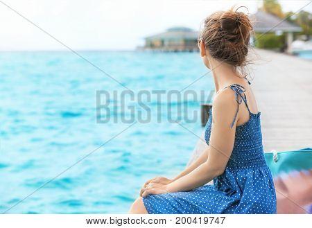 Beautiful young woman sitting on pontoon at sea resort