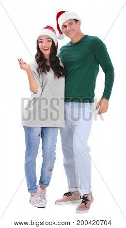 Happy young couple in Christmas hats on white background
