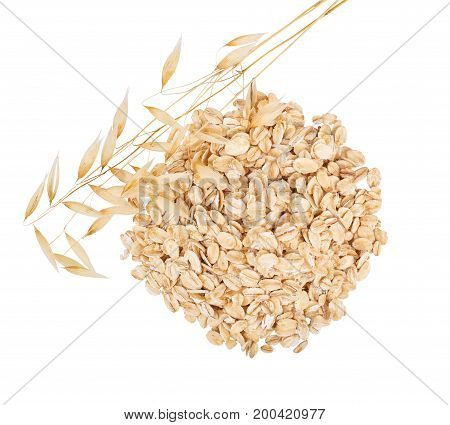 heap of oat flakes and ripe oat ears isolated on white background with clipping path top view. Uncooked oatmeal