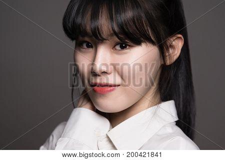 Studio portrait of Asian woman looking at camera