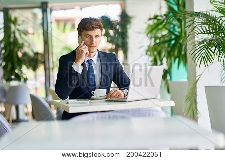 Portrait of handsome young gentleman working in cafe during coffee break , speaking by phone and using laptop