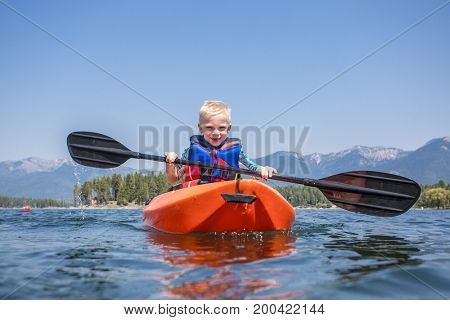 Young Boy paddling a kayak on a beautiful mountain lake. Low angle view in the water