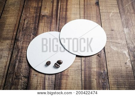 Photo of two blank white beer coasters on vintage wooden table background. Responsive design mockup. Template for your design.