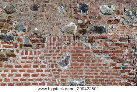 Brick wall with cobblestones background. Old grungy brickwork texture.