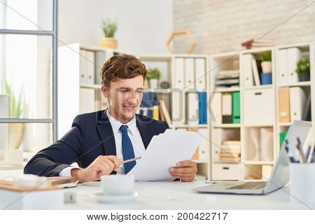 Portrait of smiling young businessman working at desk in office,  analyzing documentation