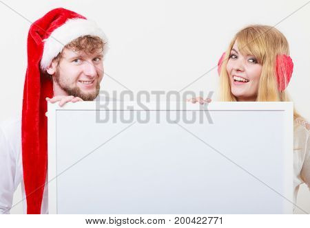 Couple woman and man holding empty blank banner with copy space. Pretty girl in santa claus hat and handsome man in studio on gray. Christmas xmas advertisement.