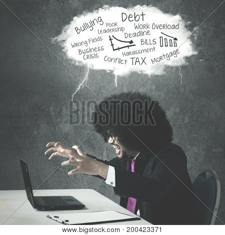 Afro businessman looks anger while shouting at a laptop and sitting under a cloud of his troubles
