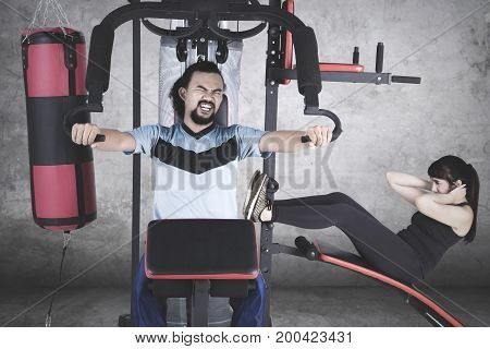 Young Afro man and his friend exercising together on weight machine while doing sit-up and pushing weights