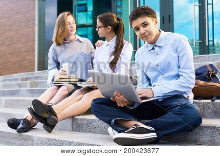 Portrait of handsome teenage student posing for photography while sitting on school stairs and doing homework with help of laptop, his classmates in uniform chatting with each other
