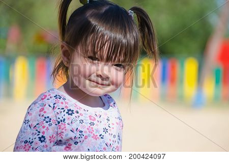 Little Cute Girl With Pigtails Looking Funny At The Camera With An Adorable And Sweet Expression