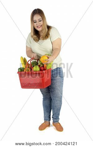 Portrait of a blonde woman holding a shopping cart full of fresh fruit and vegetables isolated on white background