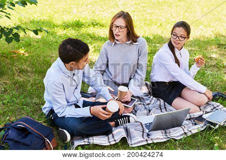 Teenage friends having picnic in sunny green park: they sitting on lawn with coffee cups in hands and discussing joint school project