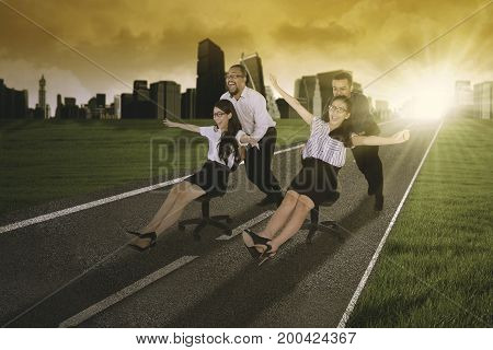 Photo of two businessmen pushing their friends on the chair while racing on the asphalt road shot at sunset time