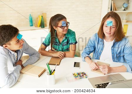 Group of cheerful teenage friends gathered together in living room and playing who am I game, pretty freckled girl trying to guess what is written on her sticky note