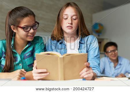 Pretty teenage students reading adventure story with interest while spending break at classroom desk, their male classmate in eyeglasses sitting behind them and looking at camera