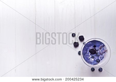 Lavender martini with berries juice on the white wooden background, copy space flat lay