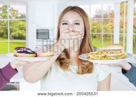 Portrait of fat woman rejects high calorie food while closed her mouth with hand