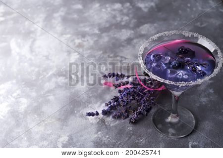 Lavender cocktail with berries on the dark stone background, copy space