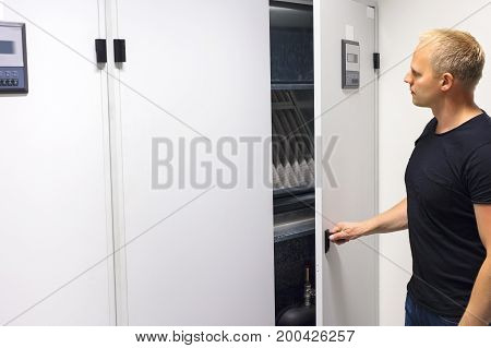 Mid adult male technician opening air conditioner cabinet in datacenter