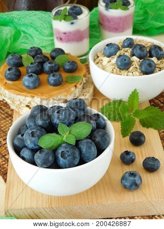 Blueberries in a ceramic bowl. Oatmeal and sandwich with peanut butter in the background. Breakfast with berries