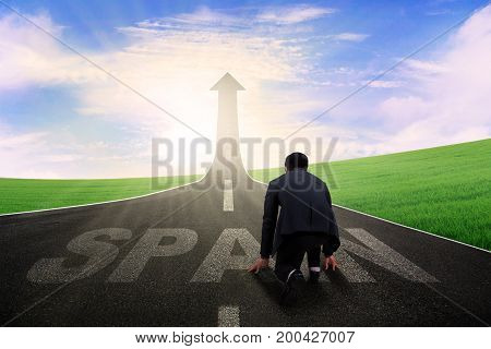 Back view of businessman kneeling on the road and ready to chase his success in the Spain country