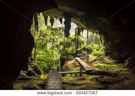 Cave entrance with plank walk and pavillion, green trees outside, in Niah National Park, Niah Cave in Sarawak Malaysia