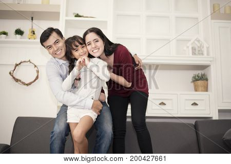 Three Happy family's members in happy mood with hug, smiling together Mom, Dad and daughter acting ing happiness concept