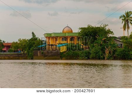 Landscape View Of The City And Sarawak River. Small Traditional Local Mosque. Kuching, Borneo, Malay