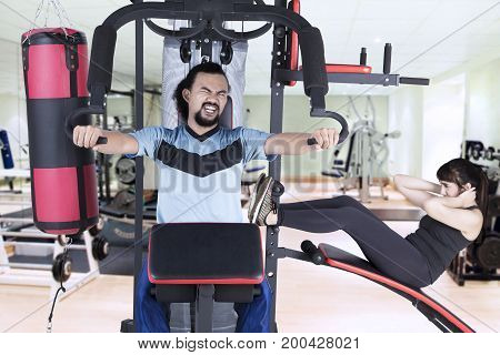 Two young multiracial people exercising on weights machine while pushing weights and doing sit-up