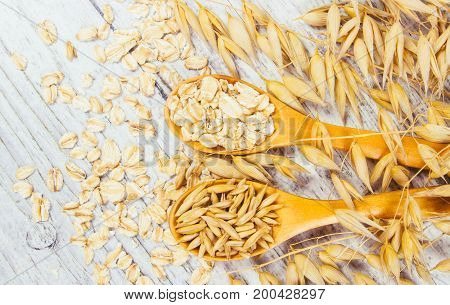 Raw Oat Flakes On A Wooden Table - Closeup.