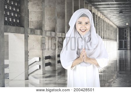 Picture of a beautiful Muslim woman smiling at the camera with welcoming gestures while standing in the mosque