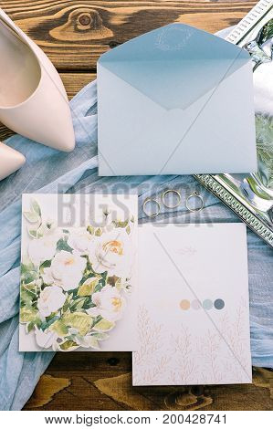polygraphy, nuptial, tenderness concept. magnificent flatlay of pastel shades. wedding invitation, two post cards with floral design. three golden rings and soft pink shoes of bride