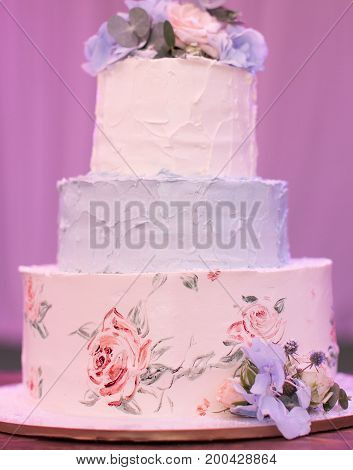 bakery, celebration, engagement concept. wonderful three-tiered wedding cake in light tender pastel shades decorated with painted roses on the first tier and natural flowers on the top