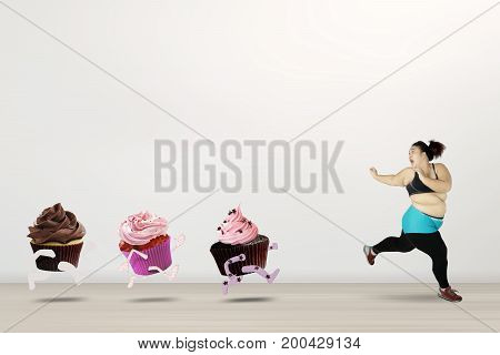 Diet concept. Overweight woman trying to lose weight by refusing junk foods and run away from cupcakes with fear expression