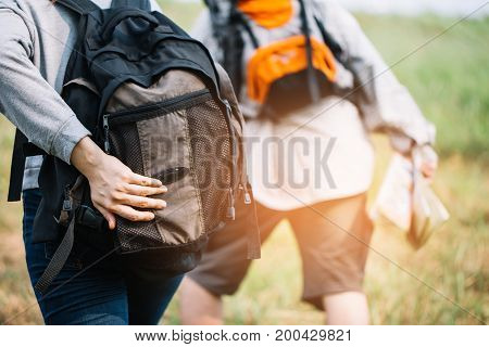 Group Of Backpacking Hikers Going To Mountain Top And Navigating By Map. Backpackers Or Hikers Trave