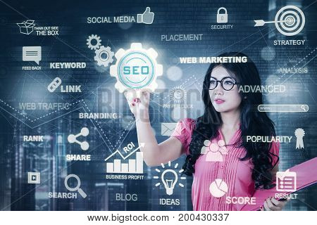 Picture of a pretty businesswoman wearing glasses and pressing a virtual SEO button. SEO concept