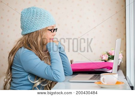 Online trader or beautiful charming girl entrepreneur or young woman freelancer use iaptop for work her job in coffee shop. Nomad worker conceptual.