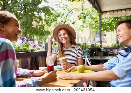 Group of young people chatting at lunch in outdoor cafe on sunny summer day, all laughing and smiling