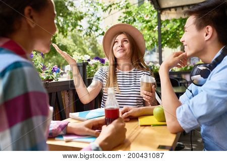 Group of three students enjoying lunch in cafe outdoors, laughing and chatting at table with books together, gesturing actively