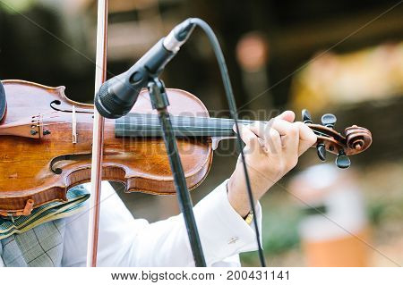 entertainment, music, culture concept. male violinist with beautiful tender hands dressed in white dizzying costume playing the violin, wooden delicate string instrument