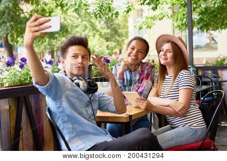 Multi-ethnic group of three  happy friends taking smartphone selfie in outdoor cafe. Asian man holding camera