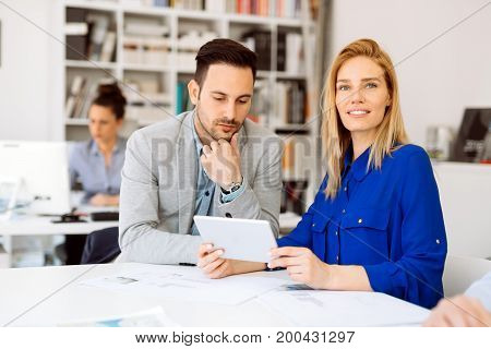 Colleagues discussing ideas on tablet in office