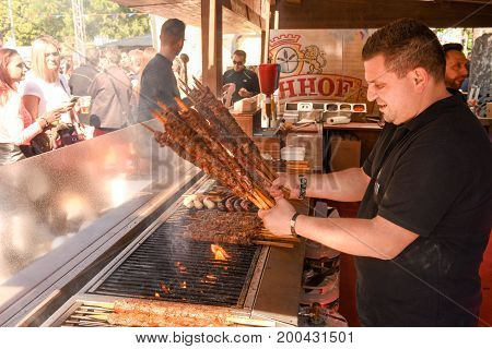 Cook Preparing Grilled Meat Skewers At Street Food Festival