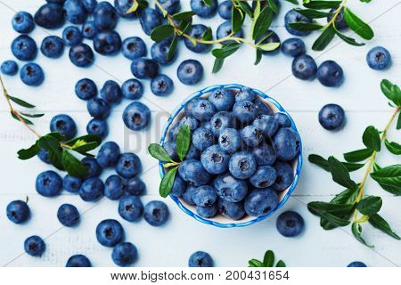 Blueberry or great bilberry in bowl on blue wooden table top view. Organic superfood and healthy nutrition.