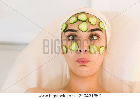Cucumber slices on eyes. Young woman with facial mask of cucumber in beauty salon. Girl grimaces and squinting
