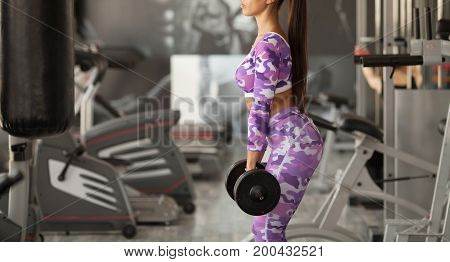Body and mind workout in loft fitness studio. Closeup on fitness woman taking dumbbell in urban loft gym
