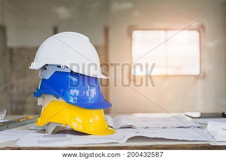 The White, Blue And Yellow Safety Helmet Stacking On Table With The Blueprint And Measuring Tools  A