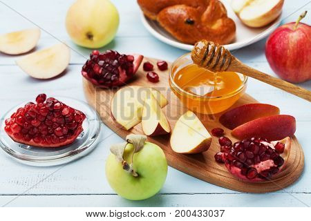 Honey apple slices pomegranate and hala serve on wooden board. Table set with traditional food for Jewish New Year Holiday Rosh Hashana.