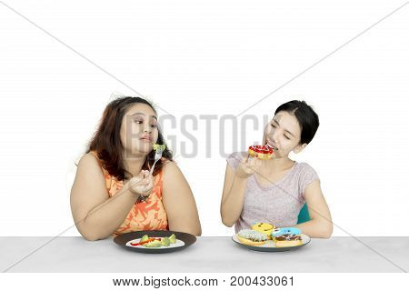 Lose weight concept. Young woman eating donuts while mocking her overweight friend eat salad